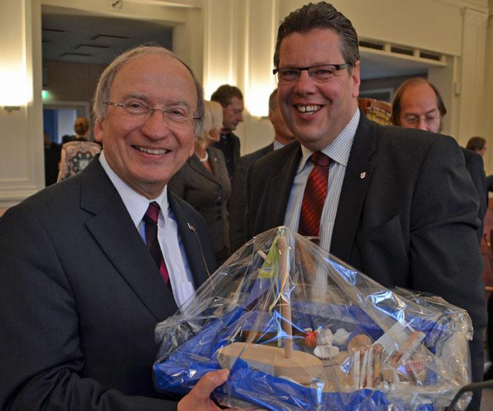 """Der stellvertretende Landrat Claus Peter Dieck übergibt als Geschenk seiner Fraktion eine liebevoll verpackte Geldspende für die Initiative """"Alle-in-einem-Boot""""."""